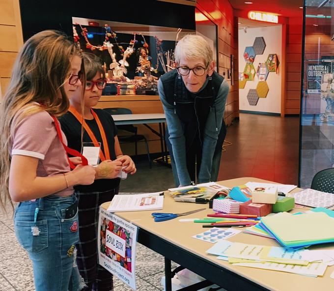 Meg Pradelt with the Soul Box Project shows two young girls how to make the origami style boxes at the Joel D. Valdez Main Library on Jan. 8. - AUSTIN COUNTS