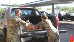 Troops place a food box and a sack of potatoes into the back of a truck during Monday's drive-thru food bank at Kino Veteran's Memorial Stadium located at 2500 E Ajo Way. Today is the first day of The Community Food Bank of Southern Arizona's drive-thru service at the new location. - AUSTIN COUNTS