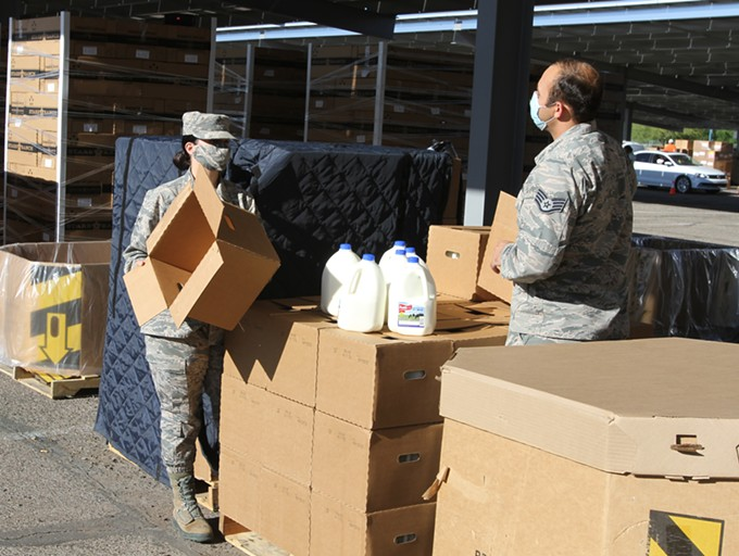 National Guard troops have a conversation while opening boxes of milk during a drive-thru food bank at Kino Stadium located at 2500 E Ajo Way. - AUSTIN COUNTS