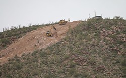 Earthmoving equipment clears a path up Monument Hill in Organ Pipe Cactus National Monument, just west of Lukeville. Advocates and Tohono O'odham Nation officials are concerned about damage to the environment, lands sacred to indigenous people and potential impact on migrating animals. - ANNABELLA PIUNTI/CRONKITE NEWS