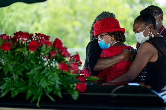 Janet Clark, left, embraces her sisters Rogers, middle, and Noel Fluence, right, after the funeral service for Williams, their brother, on May 18, 2020. Williams contracted COVID-19 while incarcerated at the Louisiana State Penitentiary at Angola. (Kathleen Flynn/ProPublica)