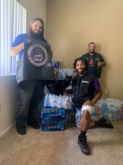 Jaylon Sesay—a.k.a. Prospect Jay—with the Sho Ryders Tucson Chapter president and vice president pose with the plethora of water bottles they plan to distribute across Tucson this weekend. - SHO RYDERS MOTORCYCLE CLUB