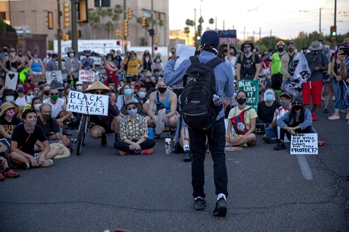 One of the protesters gives a speech to the crowd as they sit and rehydrate at the corner of Congress Street and Granada Avenue in Downtown Tucson on Saturday, July 4, 2020. After the speech, the protesters marched through the narrow streets of downtown where their voices echoed off the buildings and the ground vibrated under their stomping feet. - ALAN SCOTT DAVIS