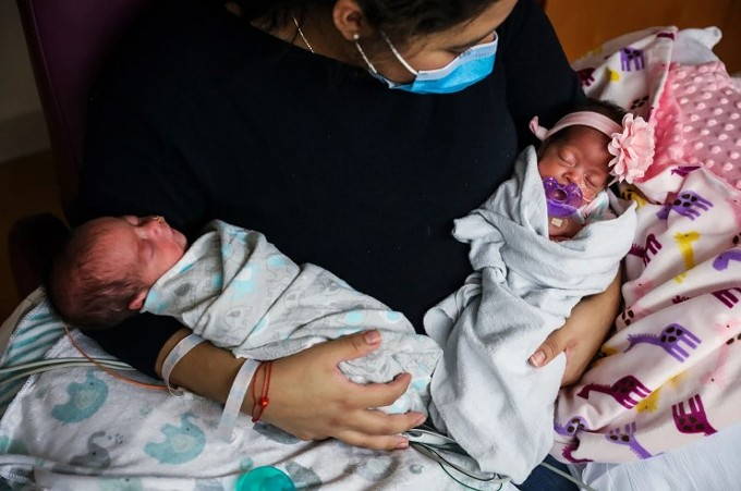 Lissbeth Hernandez holds her twins in the NICU at Tufts Medical Center in Boston on May 13. Hernandez became severely ill with COVID-19 and was intubated shortly before delivering. (Erin Clark/The Boston Globe via Getty Images)