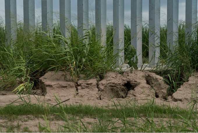 Gashes and gullies at the fence's foundation show potentially dangerous erosion. (Verónica G. Cárdenas for The Texas Tribune/ProPublica)