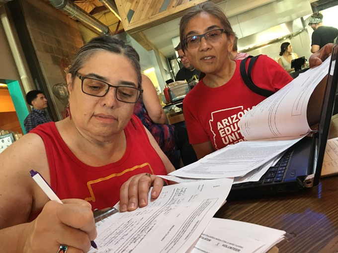 Tucson High School teachers Marea Janness (left) and Aida Castillo-Flores (right) sign up volunteers for petitioning sites at an INVESTinED gathering on June 6, 2018. - TORI TOM
