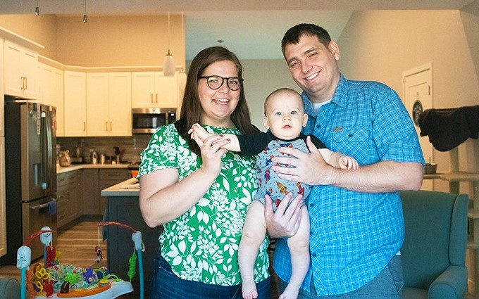 The McLean family, photographed through a window, spends the afternoon together in their Phoenix home on Sept. 15, 2020. After parents Katie and Reese tested positive for COVID-19, they took baby Jay for a swab test. It was negative, but they\u2019re convinced he had the virus. - PHOTO BY MEGAN MARPLES/CRONKITE NEWS