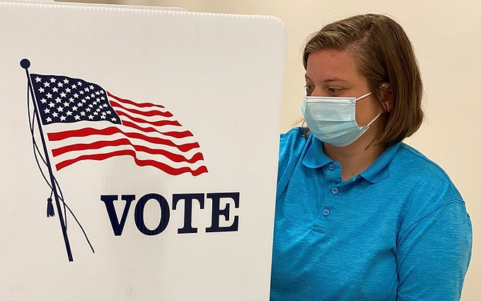 Health care is an issue in the 2020 election, but COVID-19 is not the main health care concern for voters in Arizona and other battleground states, according to a new poll. It ranked coverage for people with pre-existing conditions high. Here, a Kentucky National Guard ROTC cadet sanitizes a voting station in this June photo. - PHOTO BY CAPT. CASSANDRA MULLINS, NATIONAL GUARD, CREATIVE COMMONS