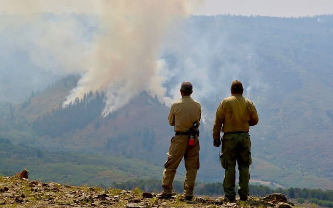Firefighters watch a controlled burn within the Grizzly Creek Fire in Colorado. The fire has burned more than 30,000 acres near Glenwood Canyon. The charred hillsides pose a flood risk for nearby areas. - PHOTO BY ALEX HAGER/ASPEN PUBLIC RADIO