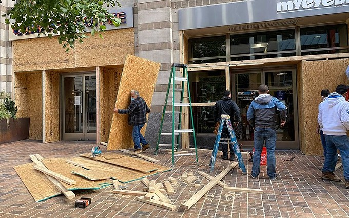 Workers board up shops and office buildings on blocks near the White House Friday, in anticipation of possible unrest after Election Day. - MYTHILI GUBBI