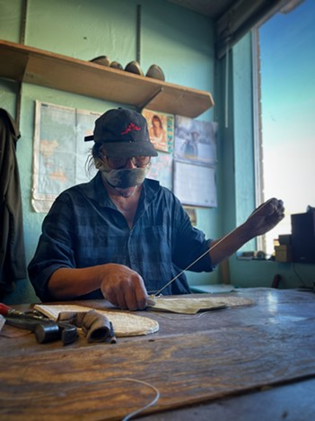 Lenny Redhouse seaming a moccasin. - BRIAN SMITH