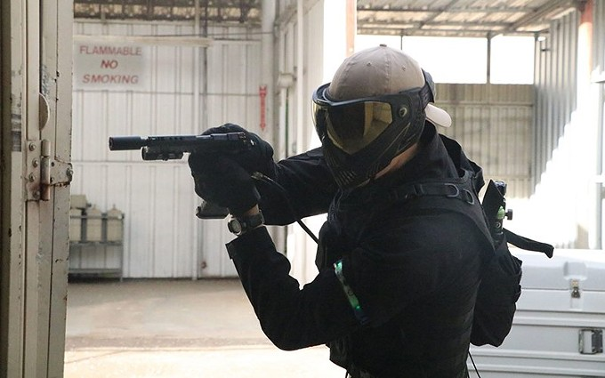 An airsoft player points an imitation gun around a corner at Dreadnought Airsoft in Phoenix on Nov. 22. The player has removed the fake gun's orange tip. - PAYTON MUSE/SPECIAL FOR CRONKITE NEWS