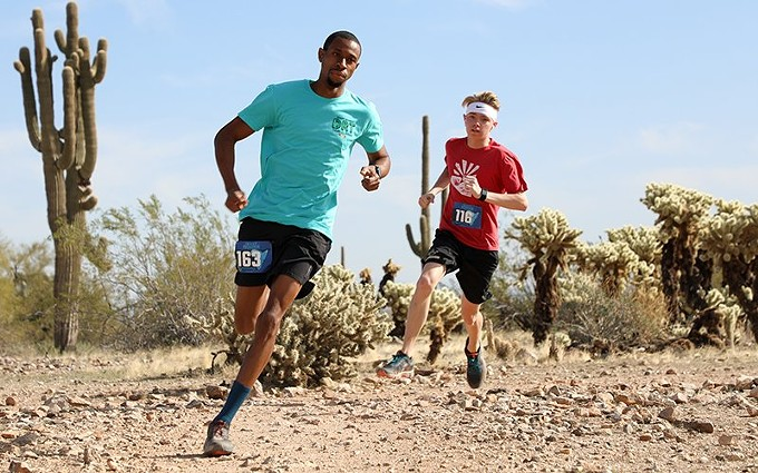 Charles Chalmers (left) and David Carson round the first turn of the course. Carson finished the race in second place for the men's 8K. - ALINA NELSON/CRONKITE NEWS