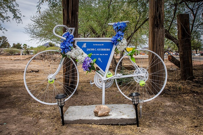 A ghost bike sits at the site of Jacob Guerrero's overdose death in Tucson. Theresa Guerrero, his mother, placed the commemorative bicycle adorned with tennis balls, symbolizing two of his favorite pastimes, to remember her son's spirit. - ALBERTO MARIANI/CRONKITE NEWS