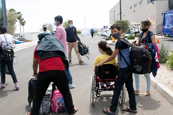 A family from Brazil, seeking asylum in the U.S., prepares to board a chartered bus that will take them from Somerton to the Casa Alitas shelter in Tucson. This family was fortunate: Men and women routinely are separated during processing at the border. - KAMILAH WILLIAMS/CRONKITE BORDERLANDS PROJECT