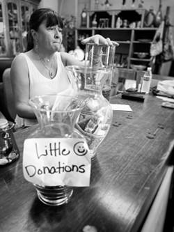 Volunteer Cheri Cordova and a tip jar. - BRIAN SMITH