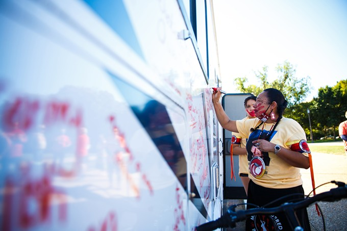 LoVina Louie, the wife of MMIW Bike Run USA organizer Duane Garvais-Lawrence, adds names to the side of the motor home that carried them on the trip. One goal of the trip was to raise $186,090 – representing what they say is the amount of women and children missing – to support MMIW help centers and families they met along the way. - DIANNIE CHAVEZ/CRONKITE NEWS