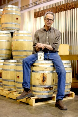 Stephen Paul proudly displays a bottle of his unaged, smoked whiskey. - HEATHER HOCH