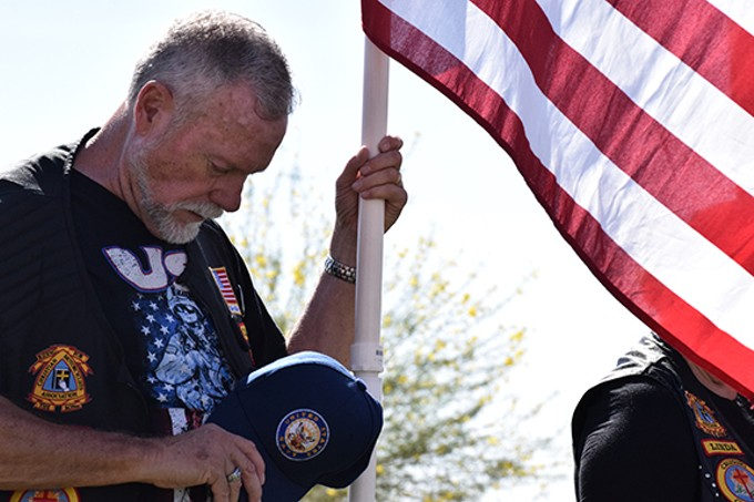 A U.S. Navy veteran and member of the Christian Motorcyclists Association bows his head in prayer during the funeral proceedings for 33 veterans, at the Arizona Veterans' Memorial Cemetery in Marana, on Oct. 28.