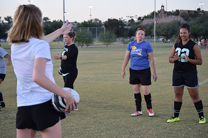 Member of Tucson's first high school girls rugby team Liz Abrego and Leilana Pye practice with Old Pueblo Thunder coach Angela Wagner.