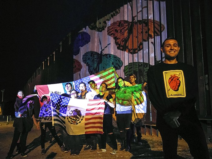 High school students from Tucson posing by art projected on the U.S.-Mexico border in Nogales, Arizona.