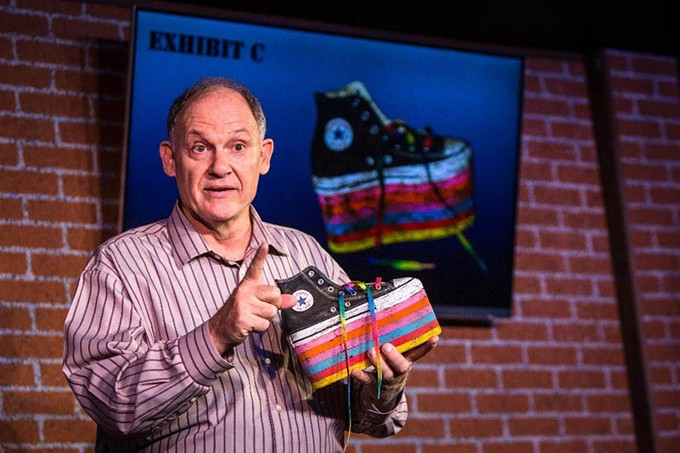 Chuck DeSantis (David Alexander Johnston), the detective assigned to investigate the disappearance of Leonard Pelkey, is holding a crucial piece of evidence - Leonard's rainbow colored platform high top sneaker.