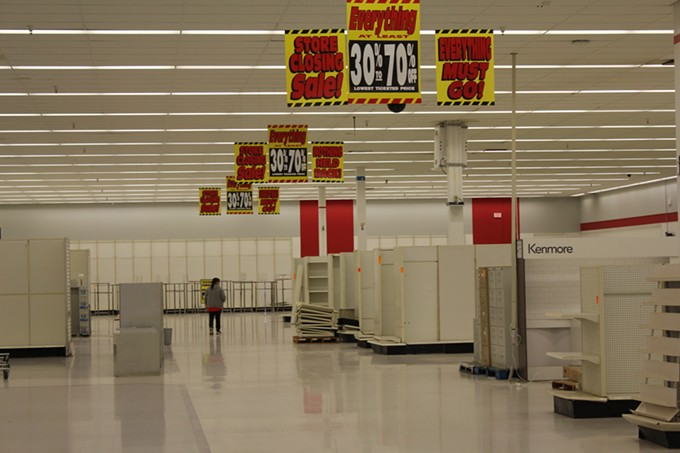 An employee walks through the empty aisles of Tucson's last Kmart.