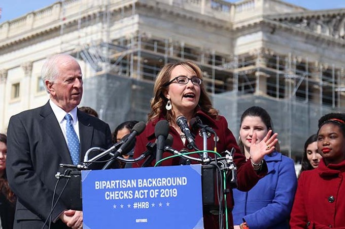 Former Arizona Rep. Gabrielle Giffords joined other victims of gun violence outside the Capitol to rally for a background check bill by Rep. Mike Thompson, D-California, left.