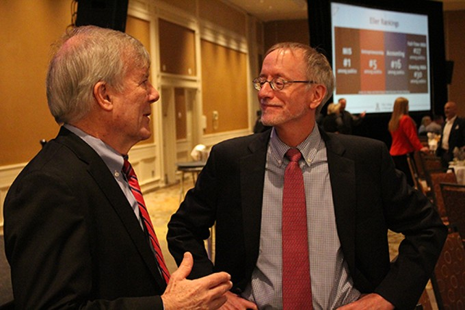 John Glassman, left, speaks to George Hammond, after they gave separate presentations about the state of the economy.