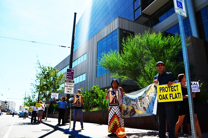 More than two dozen people protested Sen. McCain's Oak Flat move and border security bill outside Tucson Electric Power.
