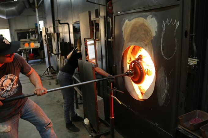 Hot Shop Glassblowing Banner: Hot Shop Director Paul Anders-Stout pulls a glass piece out of the refiring hole in Sonoran Glass School's furnace glassblowing studio.