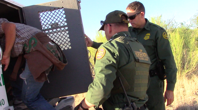 Two Border Patrol agents load one of the arrested migrants into the back of a van
