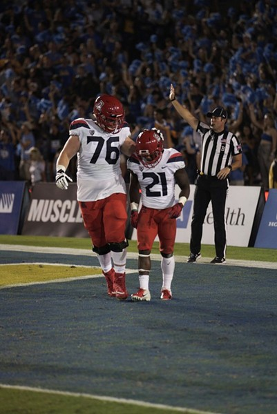 Offensive lineman Cody Creason, left, consoles running back JJ Taylor after he fumbled the football in the first half of Arizona's 31-30 loss to UCLA on Oct. 20. - CONNOR BUSS, FOREWORD FILMS