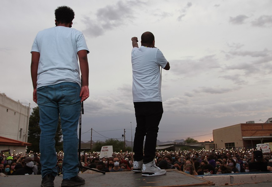 Event organizers Jahmar Anthony and Zion Givens ask the crowd to hold up a fist and observe an 8 minute and 46 second moment of silence for Geroge Floyd during the vigil at the Dunbar Pavilion on June 1, 2020. Floyd was killed Monday, May 25 after a police officer held his knee to the 46-year-old Minneapolis resident's neck for nearly nine minutes. - AUSTIN COUNTS