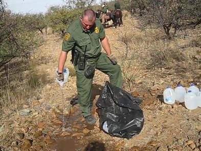 Border Patrol agent seen emptying water jugs meant for border crossers.
