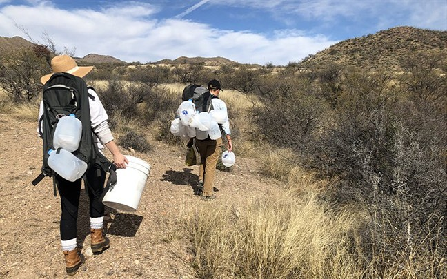 Volunteers Greena Jackson and Justine Orlovsky-Schnitzler carry empty water jugs from a supply drop site. The Jugs, which were dropped at the site two weeks earlier, appear to be slashed and emptied. - NICOLE LUDDEN