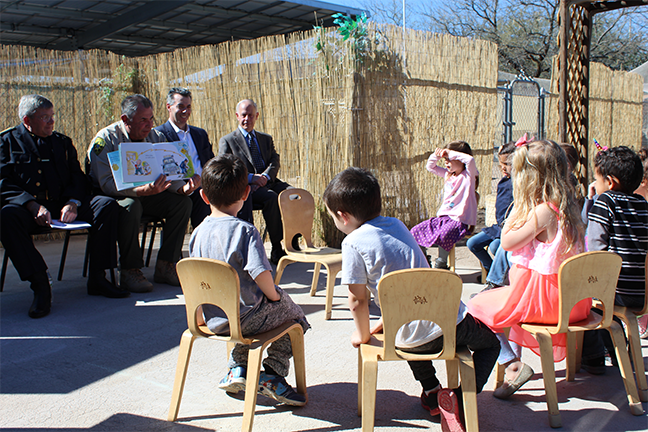 Pima County Sheriff Mark Napier reading to children at Outer Limits School alongside Oro Valley Police Chief Daniel Sharp.