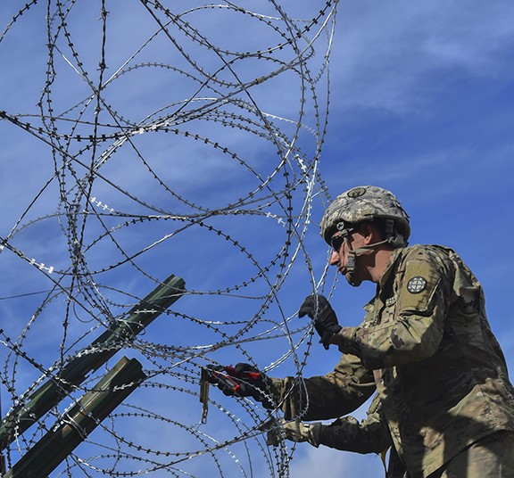 An engineer hangs concertina wire along the Nogales border in January, one of the roles that soldiers do in support of border security operations – roles critics say are unnecessary and illegal