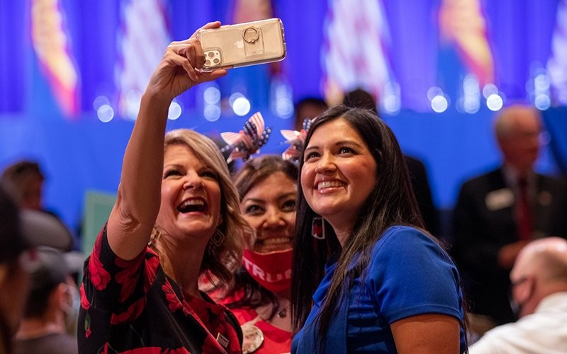 Arizona Republican Party Chairwoman Kelli Ward, left, snaps a selfie with supporters of President Donald Trump at a Latinos for Trump event in Phoenix. Like Ward, most of those attending the roundtable were maskless. - PHOTO BY LUKE SIMMONS/CRONKITE NEWS