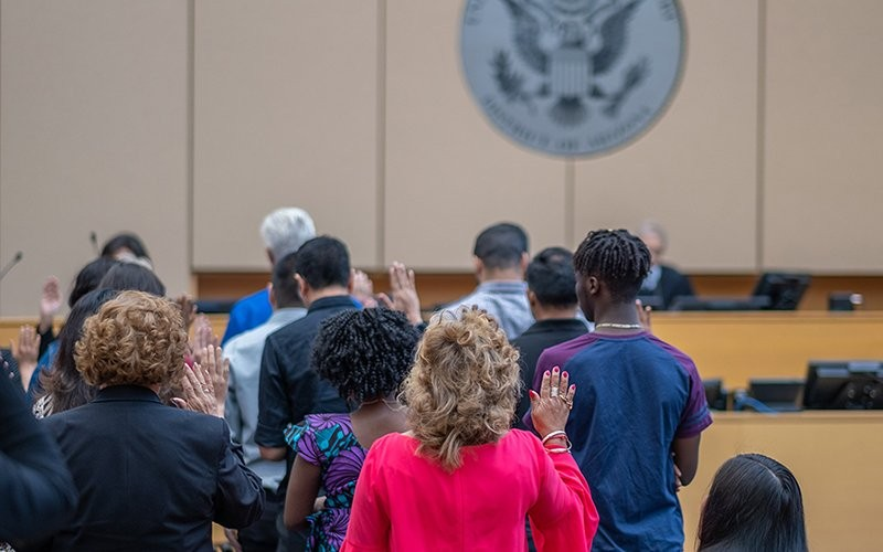 New citizens take the oath during a ceremony in Phoenix in January. Since then, citizenship ceremonies have been hit twice, first by COVID-19 shutdowns and then by cuts to the budget of the U.S. Citizenship and Immigration Services office. - FILE PHOTO BY PERLA MACIAS