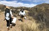 Volunteers Greena Jackson and Justine Orlovsky-Schnitzler carry empty water jugs from a supply drop site. The Jugs, which were dropped at the site two weeks earlier, appear to be slashed and emptied.