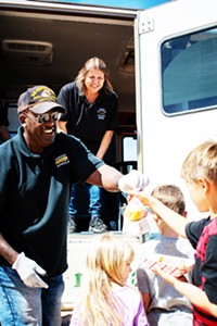 LOGAN BURTCH-BUUS - Marana bus driver Alvin Ramsey hands out free meals as part of Marana Cares Mobile